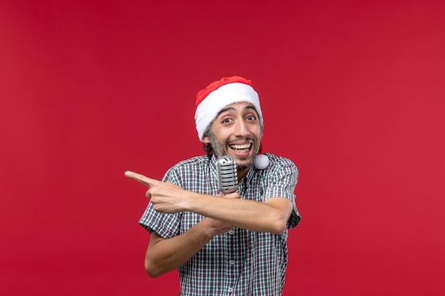 Vue de face jeune homme tenant un micro sur le fond rouge