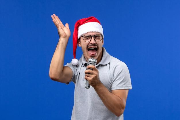Vue de face jeune homme tenant micro sur mur bleu chanteur de musique de nouvel an