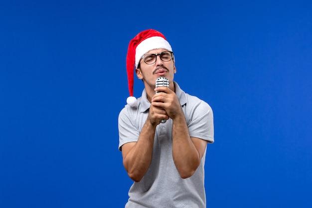 Vue de face jeune homme tenant micro sur le mur bleu nouvel an chanteur musique mâle