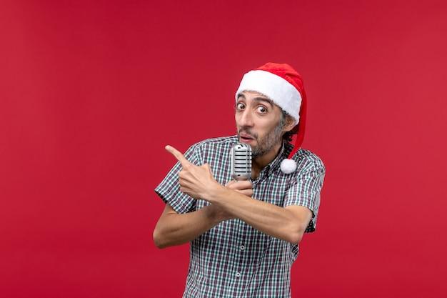 Vue de face jeune homme tenant micro sur le mur rouge émotion chanteur de vacances musique