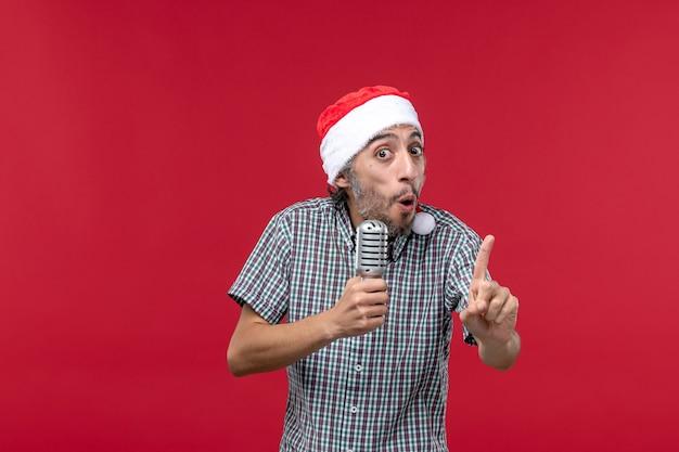 Vue de face jeune homme tenant micro sur le mur rouge émotions chanteur de vacances musique