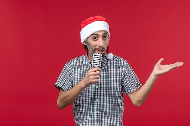 Vue de face jeune homme tenant micro sur plancher rouge chanteur modèle masculin émotion