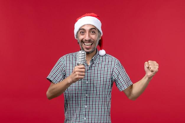 Vue de face jeune homme tenant le microphone sur le mur rouge émotion chanteur de musique de vacances