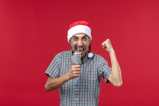 Vue de face jeune homme tenant le microphone sur le mur rouge émotion chanteur de vacances musique