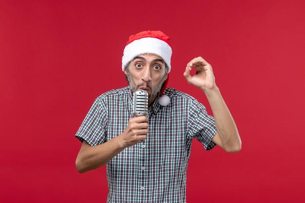Vue de face jeune homme tenant le microphone sur le mur rouge émotion vacances chanteur musique