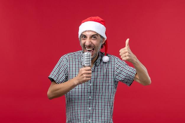 Vue de face jeune homme tenant le microphone sur la musique de chanteur de vacances émotions mur rouge