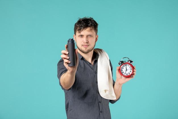 Vue de face jeune homme tenant de la mousse pour le rasage et l'horloge sur fond bleu