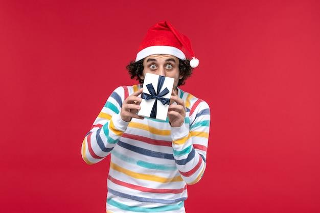 Vue de face jeune homme tenant le nouvel an présent sur le bureau rouge vacances nouvel an émotions