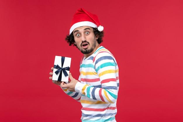 Vue de face jeune homme tenant le nouvel an présent sur le fond rouge vacances nouvel an émotion