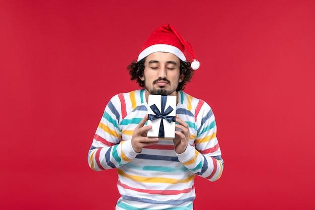 Vue de face jeune homme tenant le nouvel an présent sur fond rouge vacances nouvel an émotion