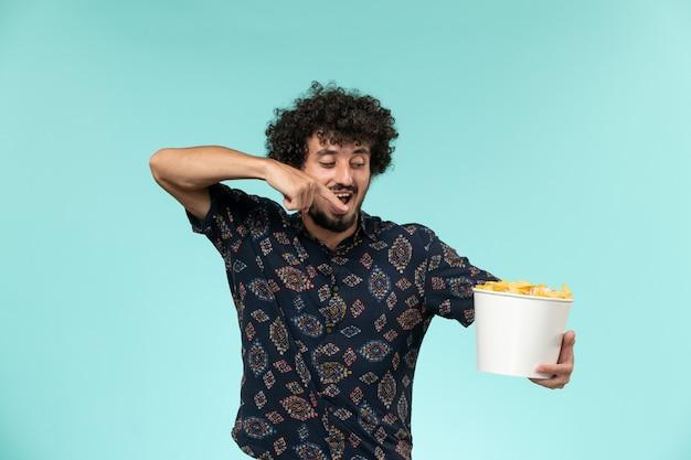 Vue de face jeune homme tenant panier avec cips sur le bureau bleu des films de cinéma à distance