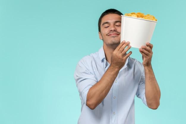 Vue de face jeune homme tenant panier avec cips et étreignant sur mur bleu film cinéma à distance mâle mâle