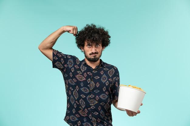 Vue de face jeune homme tenant panier avec cips et fléchissant sur le mur bleu des films de cinéma à distance