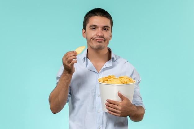 Vue de face jeune homme tenant panier avec cips manger sur mur bleu film cinéma cinéma à distance mâle