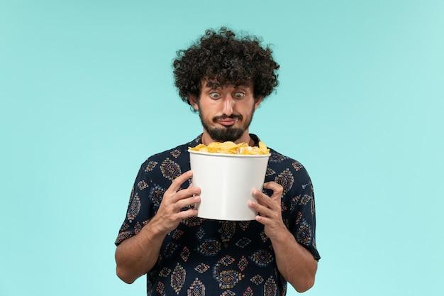 Vue de face jeune homme tenant panier avec cips sur un mur bleu cinéma cinéma films cinéma à distance