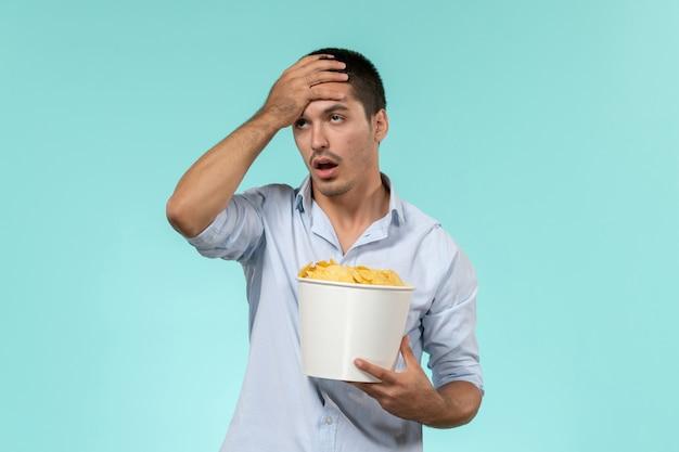 Vue de face jeune homme tenant panier avec cips sur mur bleu clair film films à distance cinéma cinéma mâle