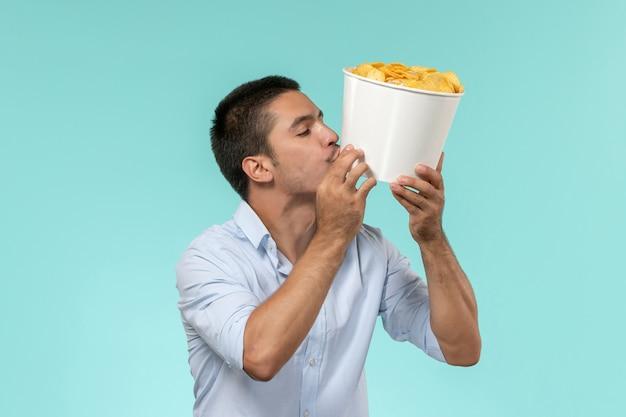 Vue de face jeune homme tenant panier avec cips sur mur bleu film cinéma cinéma à distance mâle
