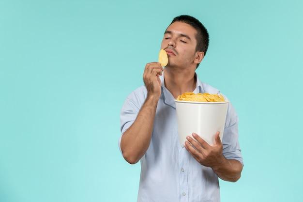 Vue de face jeune homme tenant panier avec cips sur le mur bleu film cinéma films à distance