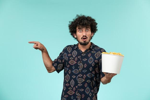 Vue de face jeune homme tenant panier avec cips sur un mur bleu films de cinéma à distance des films de cinéma