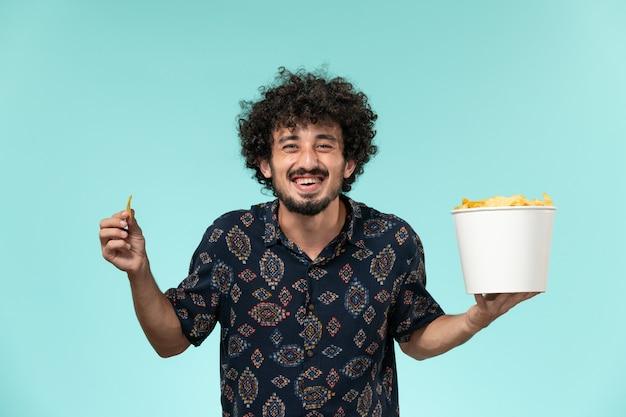 Vue de face jeune homme tenant un panier avec des cips de pommes de terre et les manger sur le mur bleu cinéma cinéma cinéma mâle