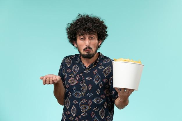 Vue de face jeune homme tenant un panier avec des cips de pommes de terre et regarder un film sur le mur bleu cinéma film cinéma mâle