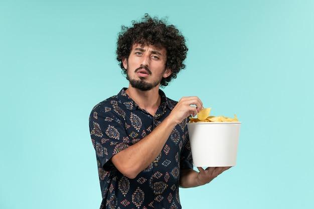 Vue de face jeune homme tenant un panier avec des cips de pommes de terre et regarder un film sur le mur bleu cinéma films cinéma mâle