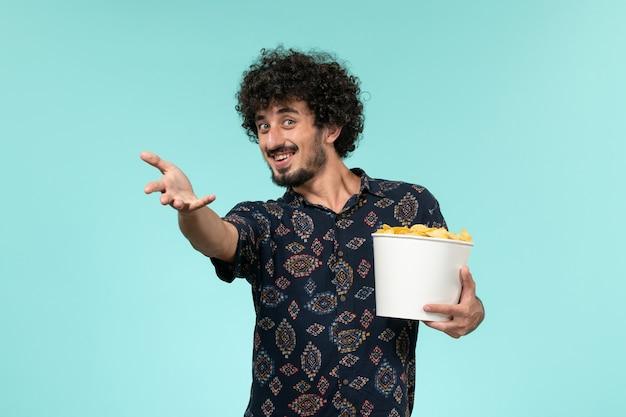 Vue de face jeune homme tenant un panier avec des cips de pommes de terre et regarder un film sur le mur bleu mâle cinéma films à distance