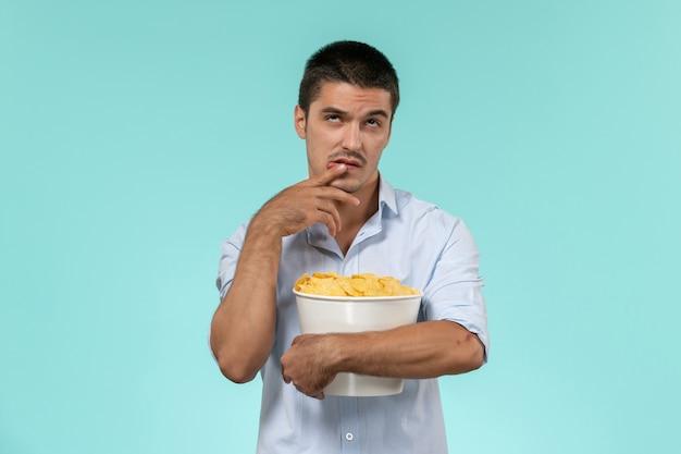 Vue de face jeune homme tenant panier avec cips et réflexion sur le mur bleu film cinéma cinéma à distance mâle