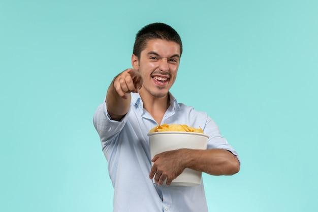 Vue de face jeune homme tenant panier avec cips et rire sur le mur bleu film cinéma cinéma à distance mâle