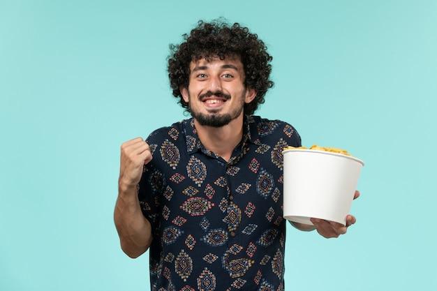 Vue de face jeune homme tenant panier avec cips et se réjouir sur le mur bleu des films de cinéma à distance