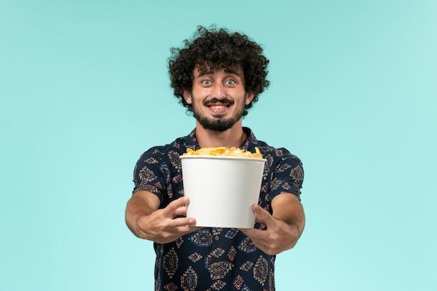 Vue de face jeune homme tenant panier avec cips et souriant sur un mur bleu cinéma cinéma cinéma cinéma à distance