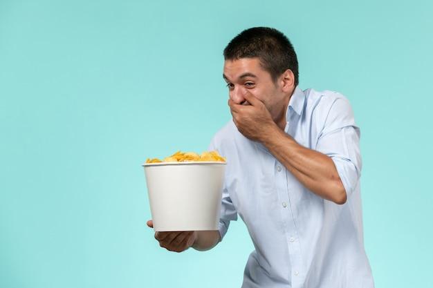 Vue de face jeune homme tenant le panier avec des croustilles et riant sur une surface bleue