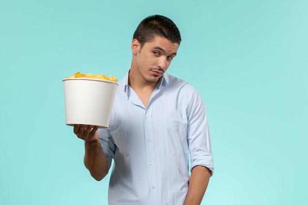 Vue de face jeune homme tenant le panier avec des croustilles sur la surface bleue
