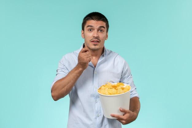 Vue de face jeune homme tenant panier avec pommes de terre cips manger et regarder un film sur un mur bleu clair cinéma à distance solitaire