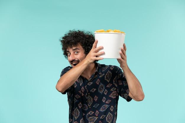 Vue de face jeune homme tenant panier avec pommes de terre cips sur mur bleu clair à distance mâle films cinéma cinéma