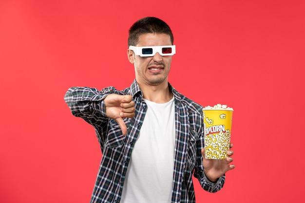 Vue de face jeune homme tenant le paquet de pop-corn sur mur rouge clair cinéma film cinéma