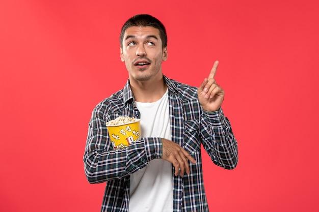 Vue de face jeune homme tenant le paquet de pop-corn et posant sur le mur rouge clair cinéma films cinéma cinéma garçon mâle