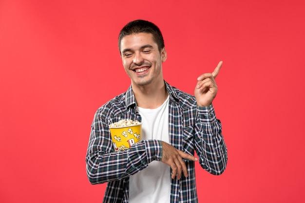 Vue de face jeune homme tenant le paquet de pop-corn et rire sur la surface rouge cinéma cinéma film film