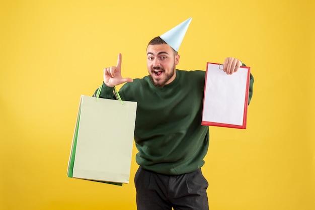 Vue de face jeune homme tenant des paquets commerciaux et note sur fond jaune