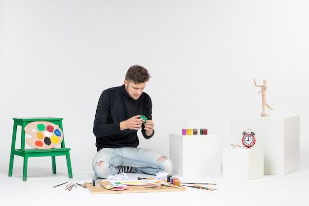 Vue de face jeune homme tenant de la peinture à l'intérieur d'une petite boîte sur un mur blanc photo art photo peinture dessiner des peintures d'artistes en couleur