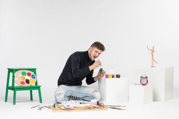 Vue de face jeune homme tenant de la peinture à l'intérieur d'une petite boîte sur un mur blanc photo art photos peinture dessiner peinture artiste couleur