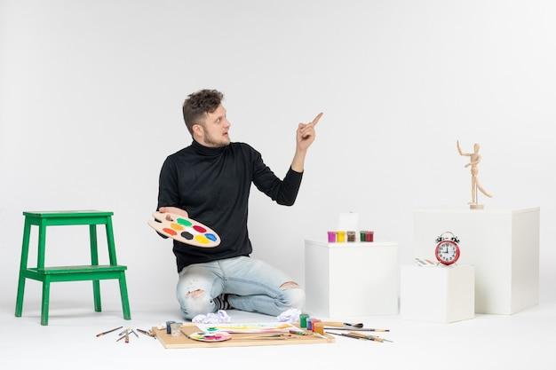Vue de face jeune homme tenant des peintures et un gland pour dessiner sur un mur blanc peinture couleur peinture artiste art dessiner homme