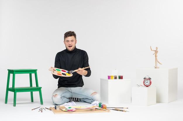 Vue de face jeune homme tenant des peintures et un gland pour dessiner sur un mur blanc peinture photo dessiner peinture artiste couleur