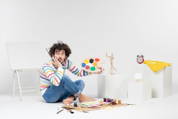 Vue de face d'un jeune homme tenant des peintures et un gland pour dessiner sur un mur blanc