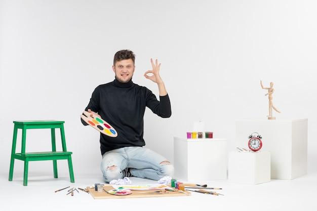 Vue de face jeune homme tenant des peintures et un gland pour dessiner sur des peintures murales blanches peinture couleur artiste art dessiner une image