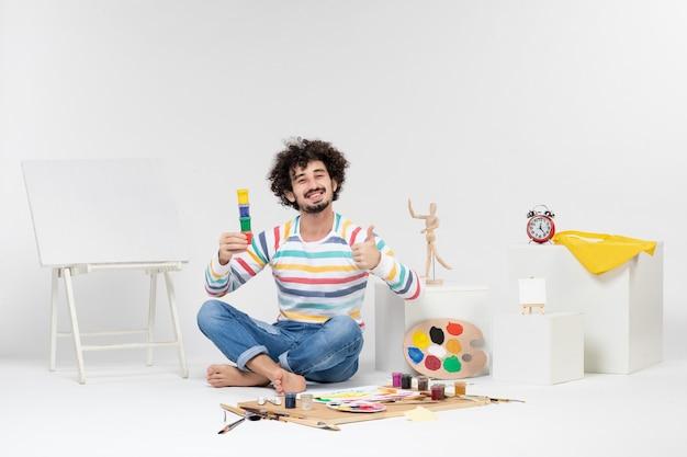 Vue de face d'un jeune homme tenant des peintures pour dessiner à l'intérieur de petites boîtes sur un mur blanc