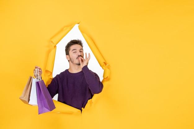 Vue de face jeune homme tenant de petits paquets après le shopping sur fond jaune modèle cadeau nouvel an présent couleur de noël