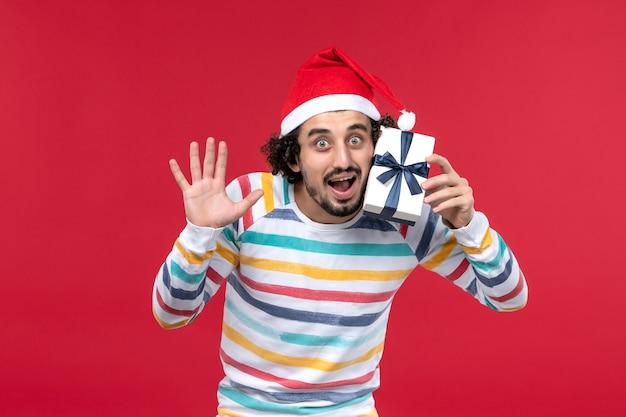Vue de face jeune homme tenant peu de cadeau sur le bureau rouge émotion rouge vacances nouvel an