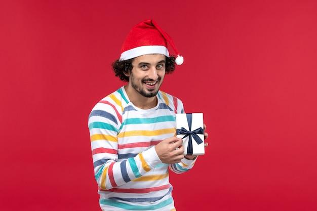 Vue de face jeune homme tenant peu de cadeau sur les émotions du mur rouge vacances nouvel an rouge