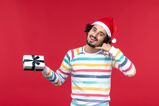 Vue de face jeune homme tenant peu de cadeau sur les émotions du mur rouge vacances nouvel an